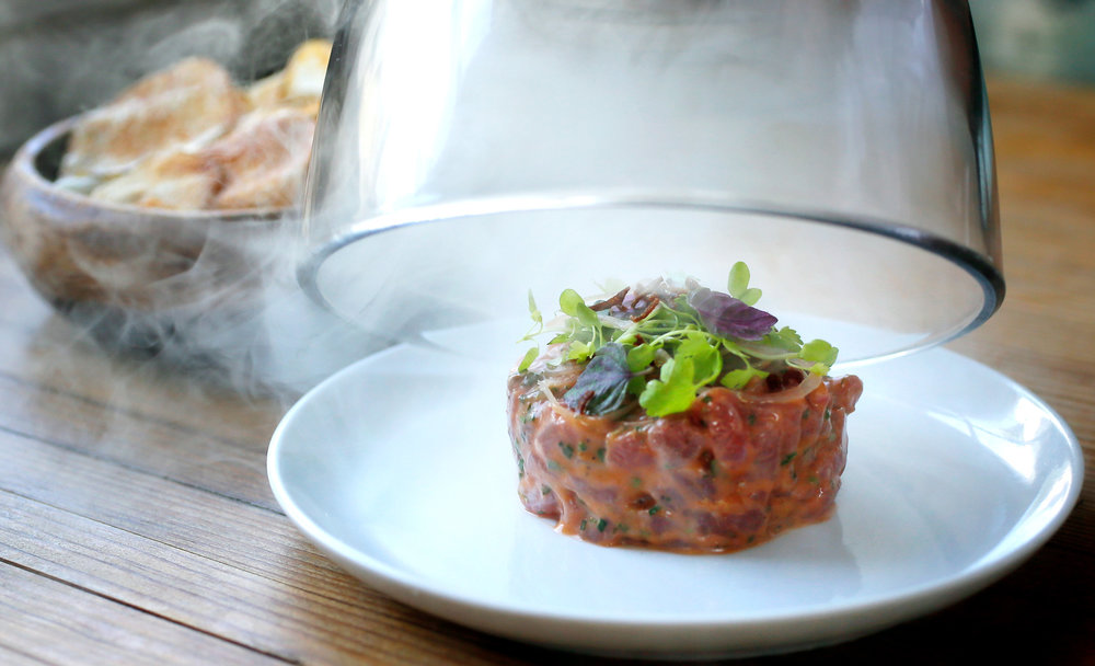 Buckhead grass fed beef tartare at Prohibition in Charleston, S.C. The dish is served to the customer encased in smoke, which is then dispersed as the lid is removed.