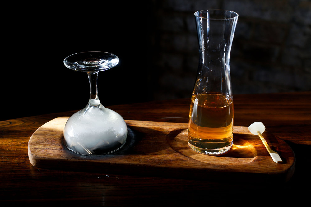 The Bohemian Business made with Bristow, barrel aged gin, Blanc vermouth, and garnished with a cocktail onion at Scarecrow in Charleston, S.C. Hickory chips are lit under the glass to produce smoke before the drink is poured by the patron.