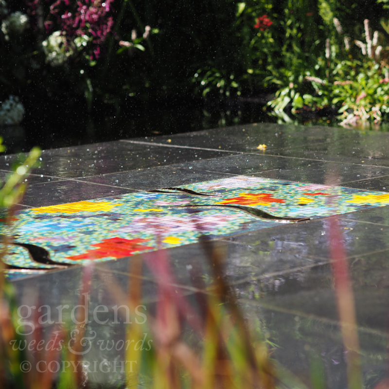 Droplets of water pattering on the slate platform and the mosaic set within.  Detail from Charlie Bloom's  Brilliance in Bloom garden  at the RHS Hampton Court Flower Show 2018