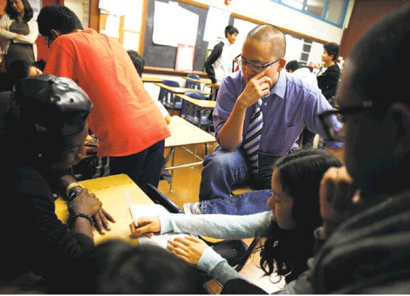 Ethnic studies teacher David Ko (center) works with students as they undertake a classroom exercise by brainstorming a topic and research questions.