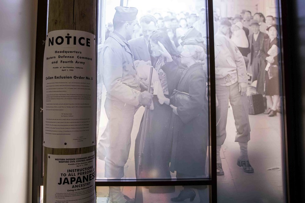 Replicas of civilian exclusion orders are tacked to a pole in front of a scene of Japanese Americans being transported from their homes.  Photo by Darren Yamashita