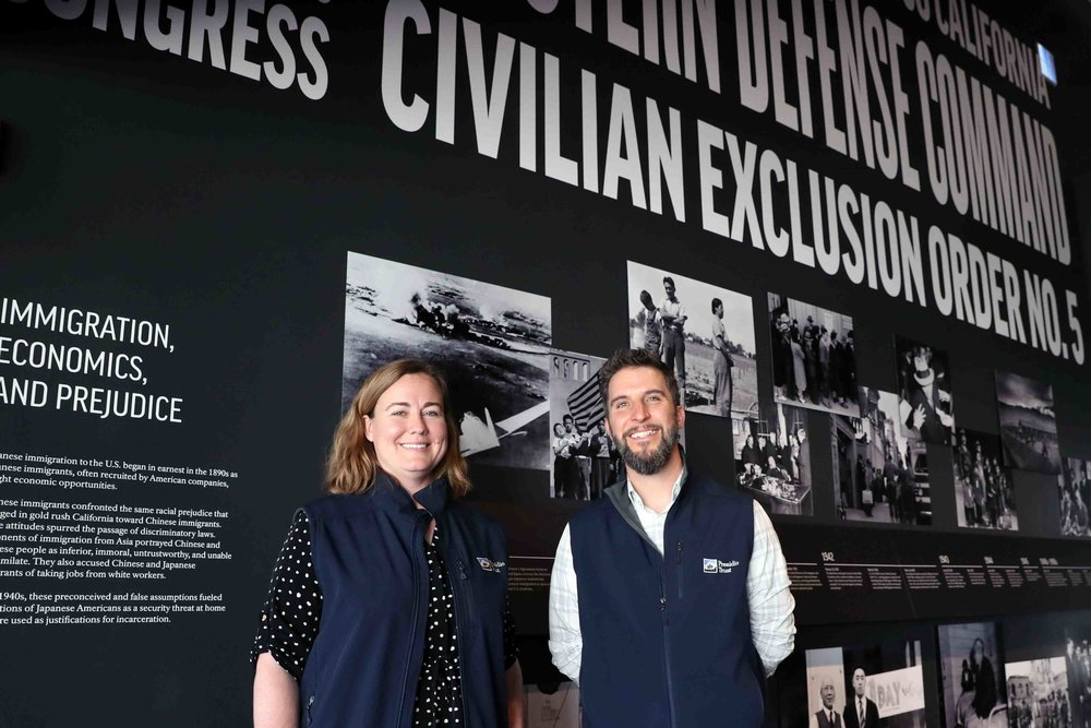 "Kathryn Inglin, Presidio associate director of external affairs, and Eric Blind of the Presidio Trust stand in front of one of the displays of the ""Exclusion"" exhibit.  Photo by Darren Yamashita"