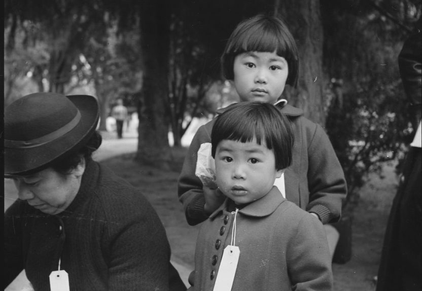 "Two children of the Mochida family are photographed who, with their parents, are awaiting evacuation bus in Hayward in 1942. The youngster on the right holds a sandwich given her by one of a group of women who were present from a local church. Piedmont Appreciating Diversity Committee's first free film showing of the season, ""And Then They Came for Us,"" on Sept. 27 is about the internment of Japanese Americans 75 years ago. (Dorothea Lange/National Archives)"