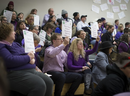 Dave and Hannah Edwards (center, holding hands), parents of a gender-nonconforming child, sat in silent protest during Tuesday's presentation. Caption via the Star Tribune coverage, photo Renee Jones Schneider.