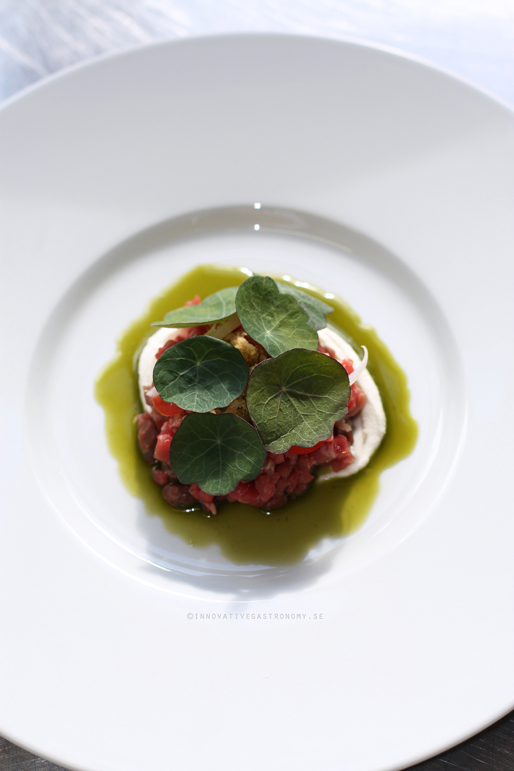 Tartar of dry aged beef, smoked cream cheese, fresh tomatoes, pickled schalotts and nasturtium