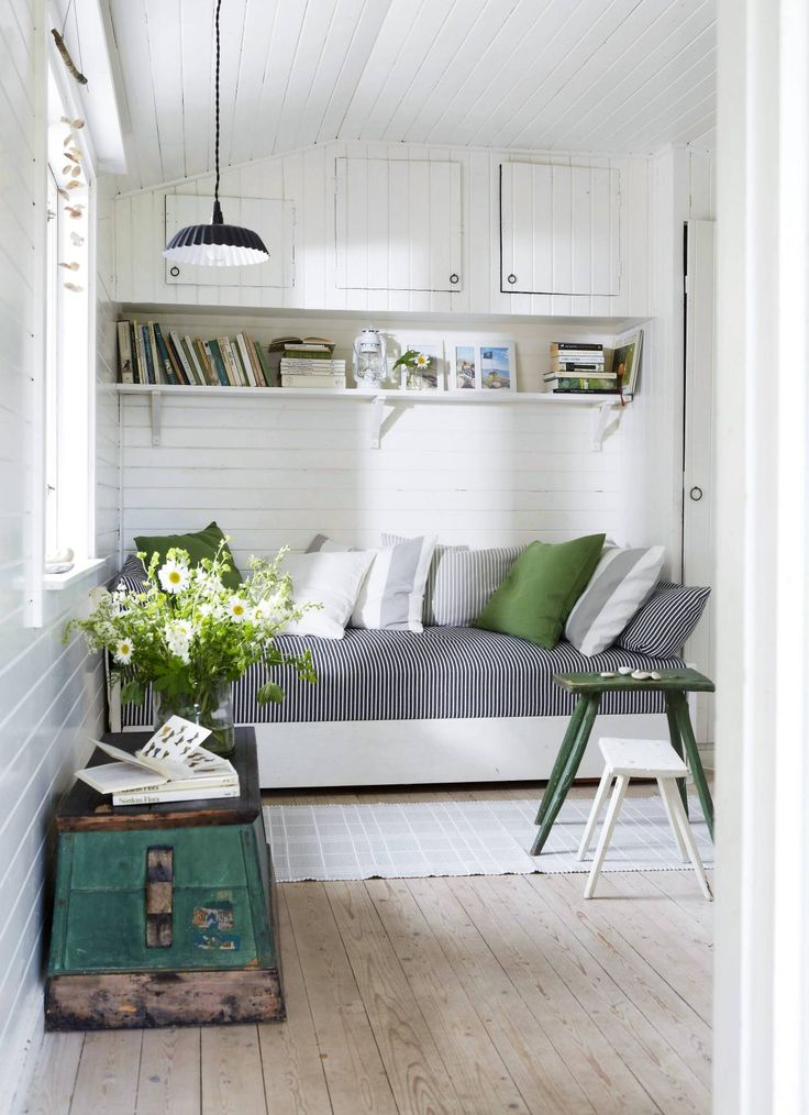 A snug space with a day bed, mixing modern textiles with antique features. Nordique loves the effect of the splash of green added to this calm white space.  Image source