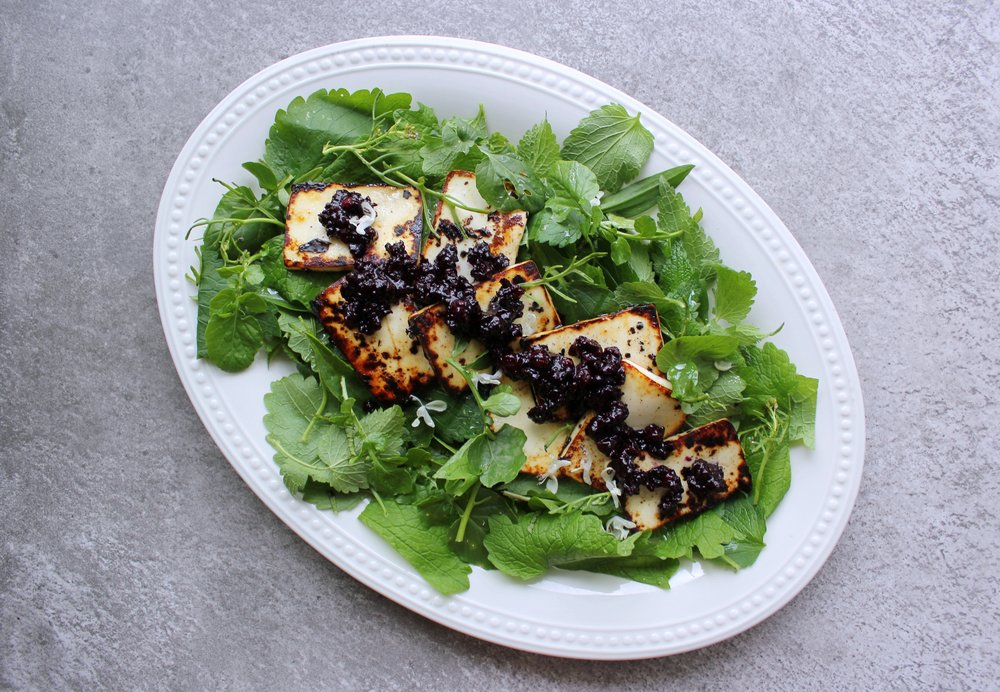 """This is a salad of wild herbs and greens, fried halloumi cheese and aronia compote."""