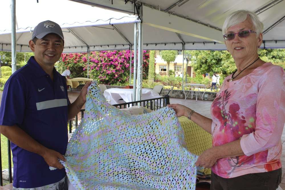 "June met Dr. Francisco while studying Spanish in San Pedro, and told the rest of us ""you've got to meet this guy."" Here, she's delivering a Canadian-knitted baby blanket, for a future safe-delivery in Francisco's clinic."
