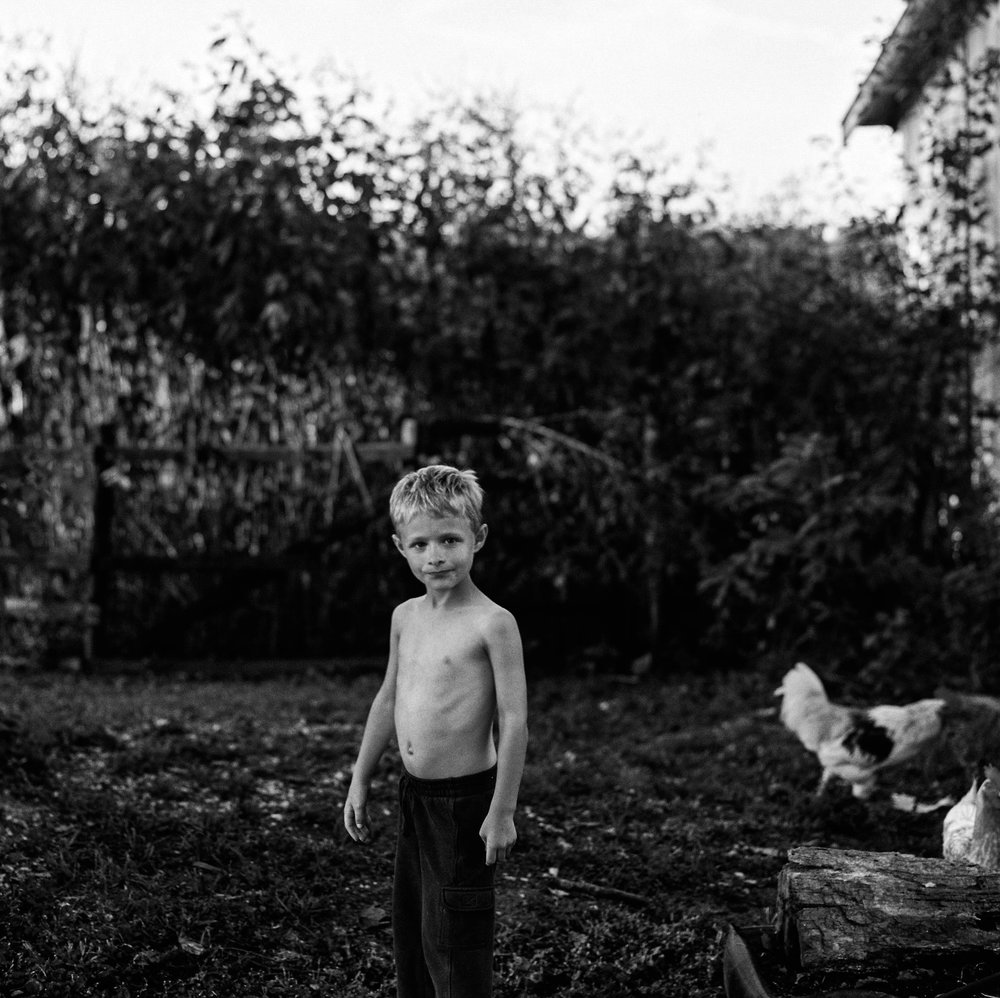 Dawson in his family's yard. At six years old, half his life has been spent here, on the Webb family farm. The first half, though, was filled with abuse that still haunts him.