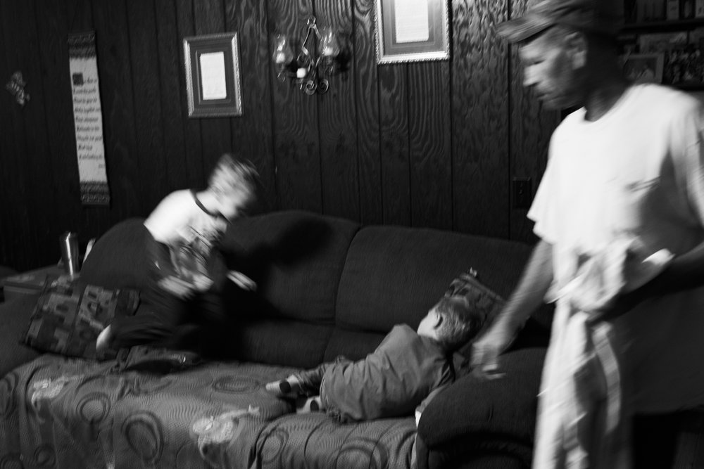 Dewayne struggles to get both brothers into bed as Alex jumps and Dawson cries on their couch.