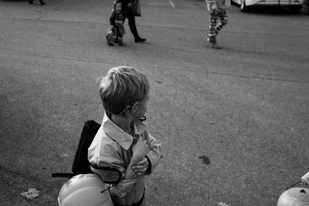 "Dressed as a ghostbuster, Dawson looks around while trick-or-treating with his family. Due to his RAD, he does not always preform well in social situations and often seems withdrawn. ""To help him socially, we make sure to get him in the community. We go to Sunday School every week so he meets kids his age and do other stuff when we can."""