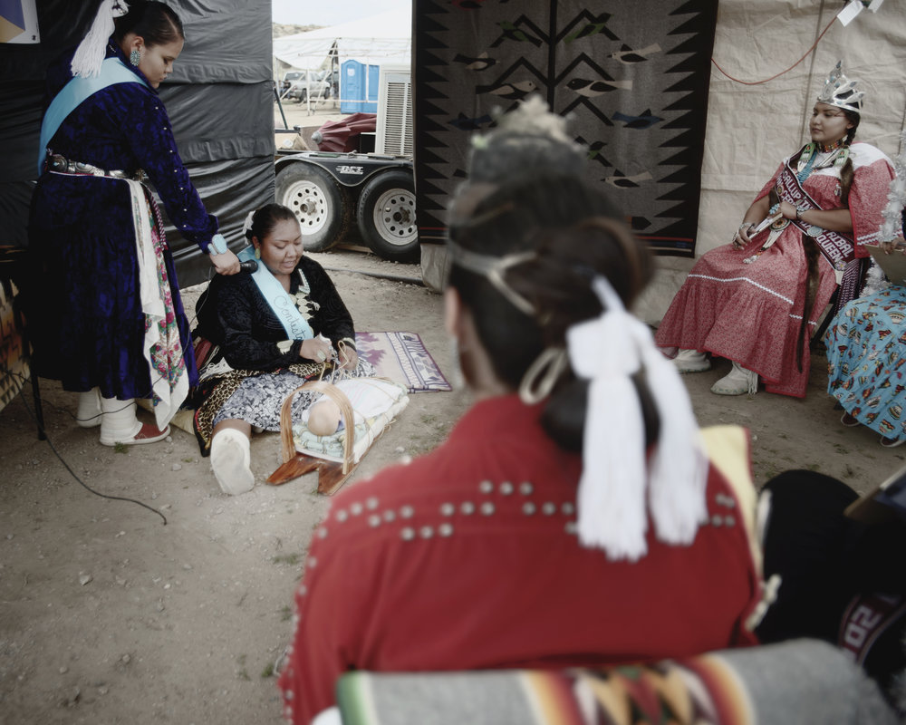 Lanirae Padilla makes a craddleboard while singing a Navajo powwow song at the Eastern Diné bi Pageant in Crownpoint, New Mexico.