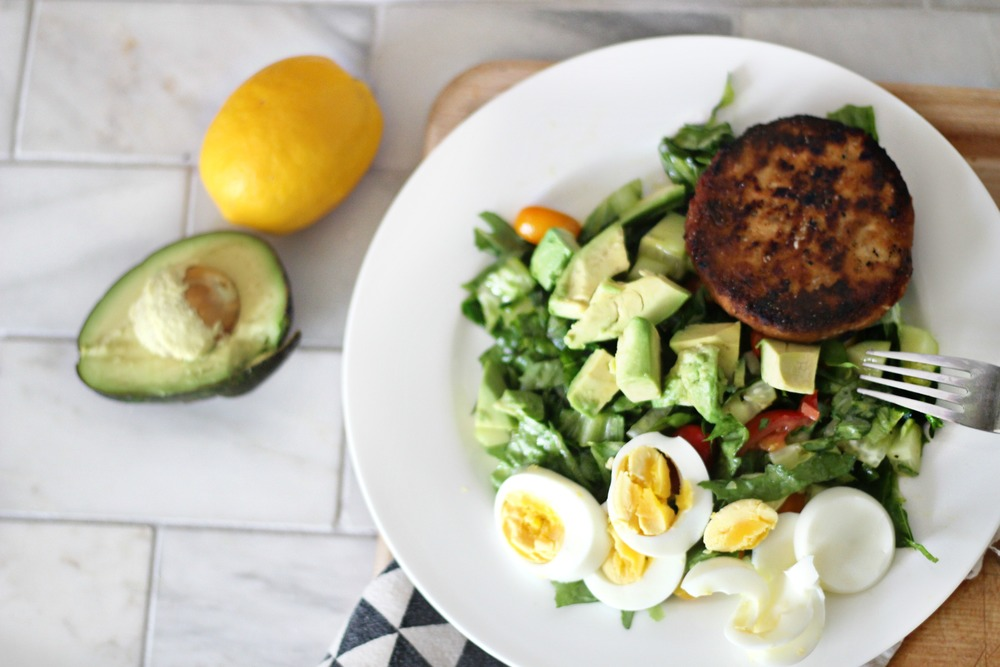Lastly, chop the hard boiled egg and avocado, place it on top of the salad along with the salmon patties.