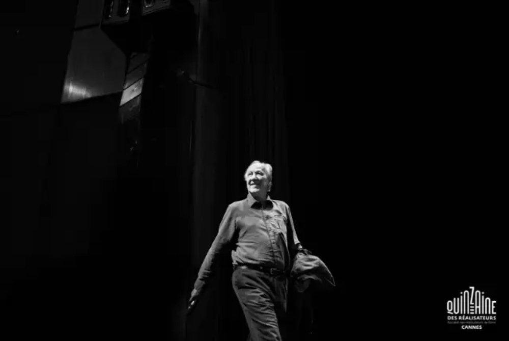"""沃纳·赫尔佐格在金马车奖颁奖现场   今年戛纳平行单元""""导演双周""""金马车奖颁给了德国导演沃纳·赫尔佐格。金马车奖是于2002年创设的颁发给杰出电影人的终身成就奖,此前获此殊荣的有阿基·考里斯马基、贾樟柯、阿伦·雷乃和简·坎皮恩等。从十五岁写出第一个剧本开始,赫尔佐格未曾停止过电影创作,迄今执导了七十一部影片。  早年被冠以""""新德国电影四杰""""之一,与施隆多夫、法斯宾德和文德斯齐名,然而相比之下,赫尔佐格的创作生涯漫长得多,涉猎也更为广泛,他摈弃对电影种类的明确划分,挣脱已有创作形式的束缚 ,用自己独特的电影语言和手法带领观众进入""""狂喜的真实""""。颁奖词上,法国电影导演协会如此描述这位七十四岁的狂人大导:    """"我们对赫尔佐格的坚持不懈的精力和非凡的创造力以及他兼顾多种形式、创作惯例和系统的能力致以敬意,他模糊了剧情片与纪录片、故事片与电视、理智和疯狂之间的分割线。""""    今年,深焦DeepFocus有幸在双周组委会的安排下,在戛纳海滩边,对这位来自巴伐利亚山区的疯狂电影老将,进行了一次专访……"""