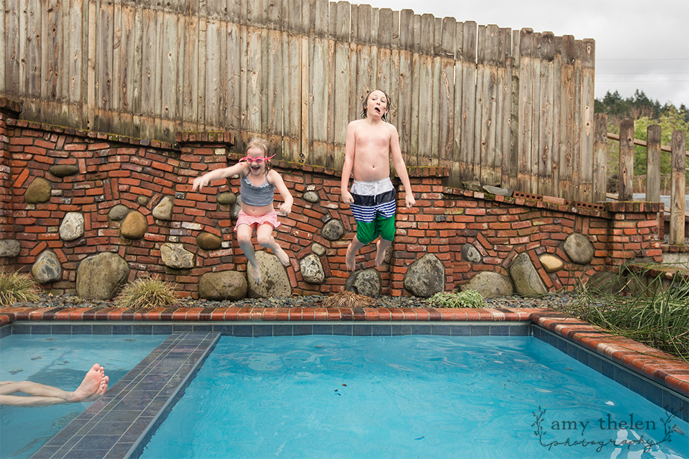 boy and girl jumping in pool