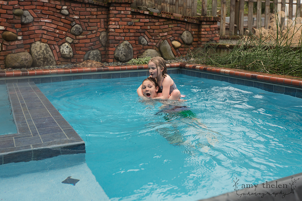 girl riding on boy's back in pool