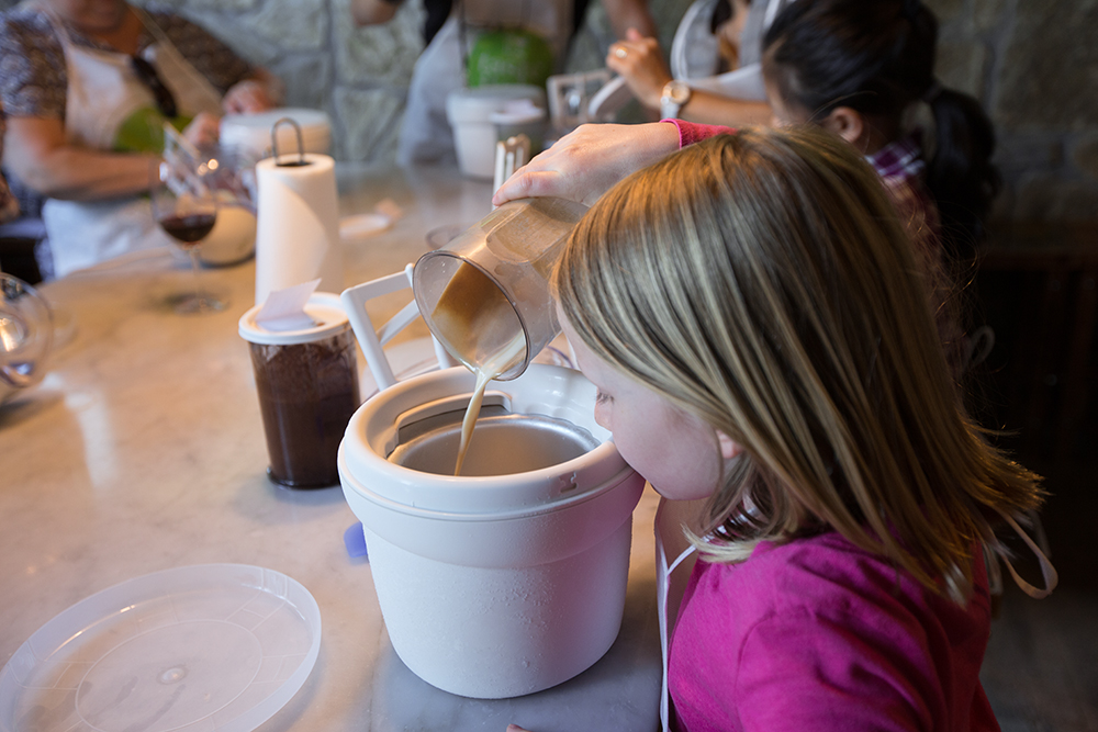 girl pouring cream mixture into ice cream maker