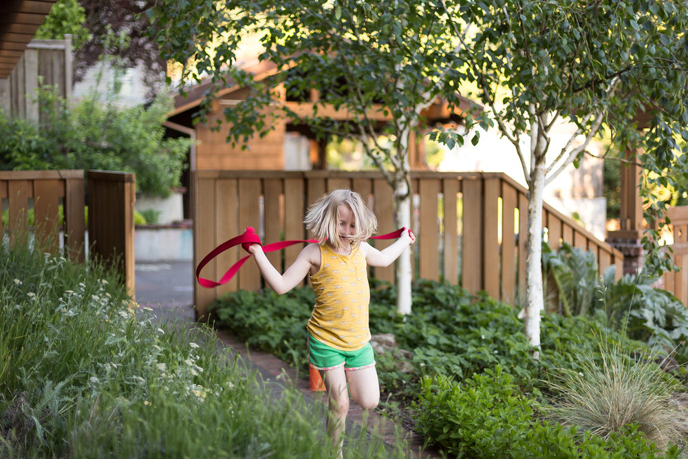 young girl jumping rope in garden