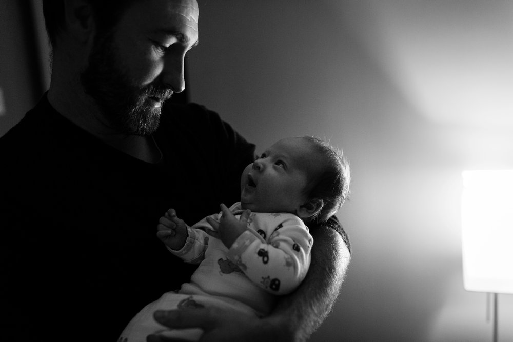 newborn baby and dad look at one another in awe