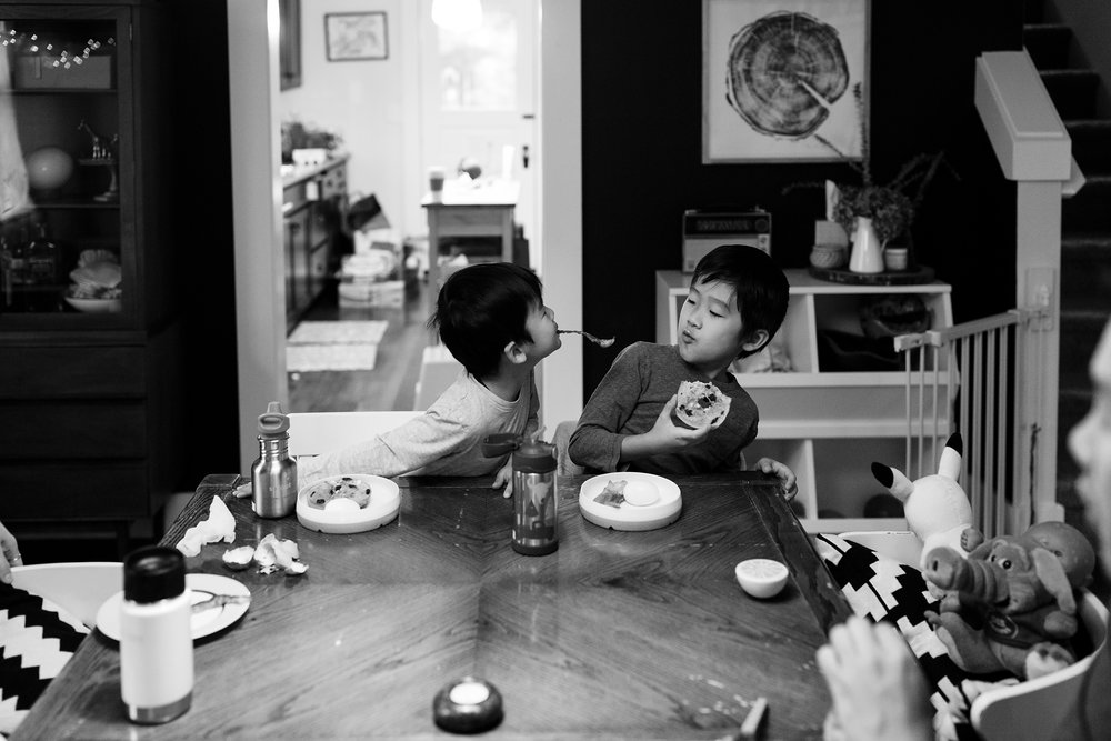 boy with fork in mouth tries to poke brother while eating breakfast