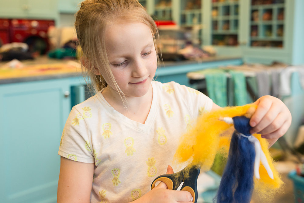 girl makes felted wool angel cutting hair in messy craft room