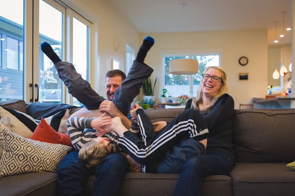 family of four belly laughing on couch