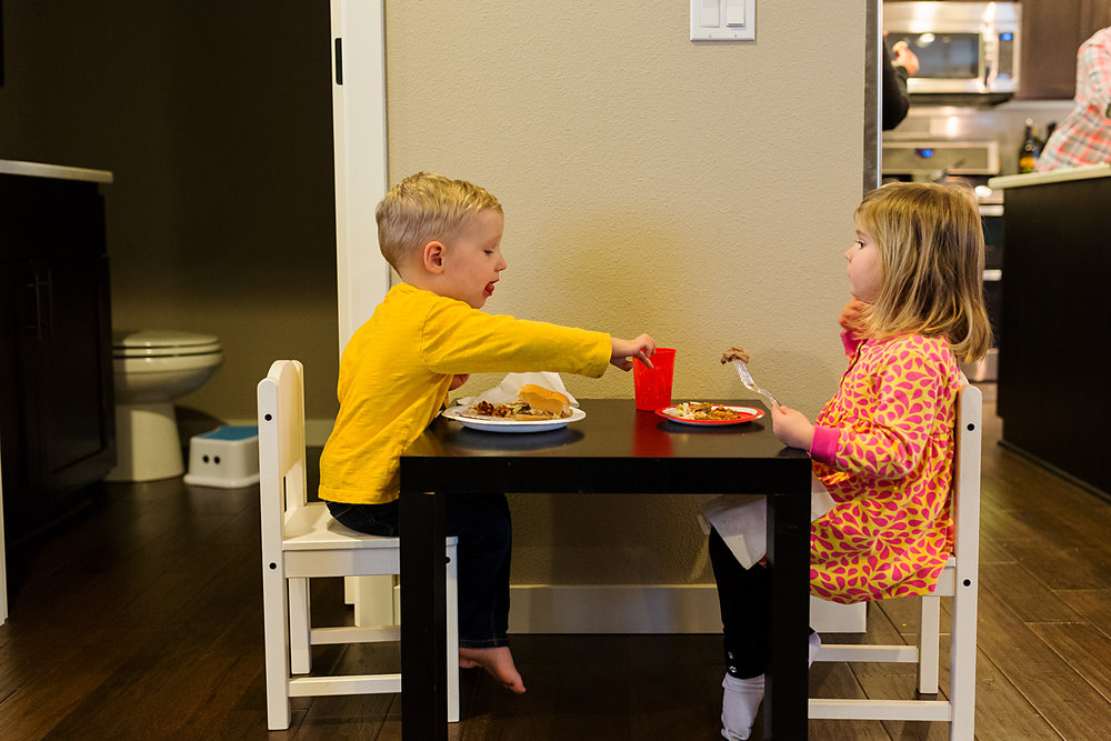 boy and girl cousins eat at kids table while boy tries to take food from girl