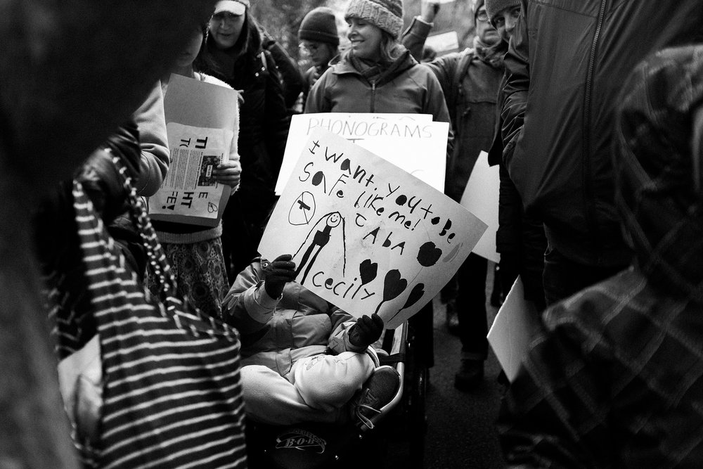 child holds handmade sign against violence