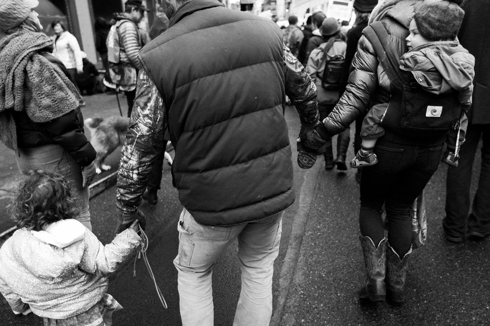 family holds hands while marching