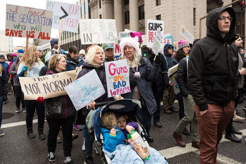 kids share pretzels in stroller while family marches with signs