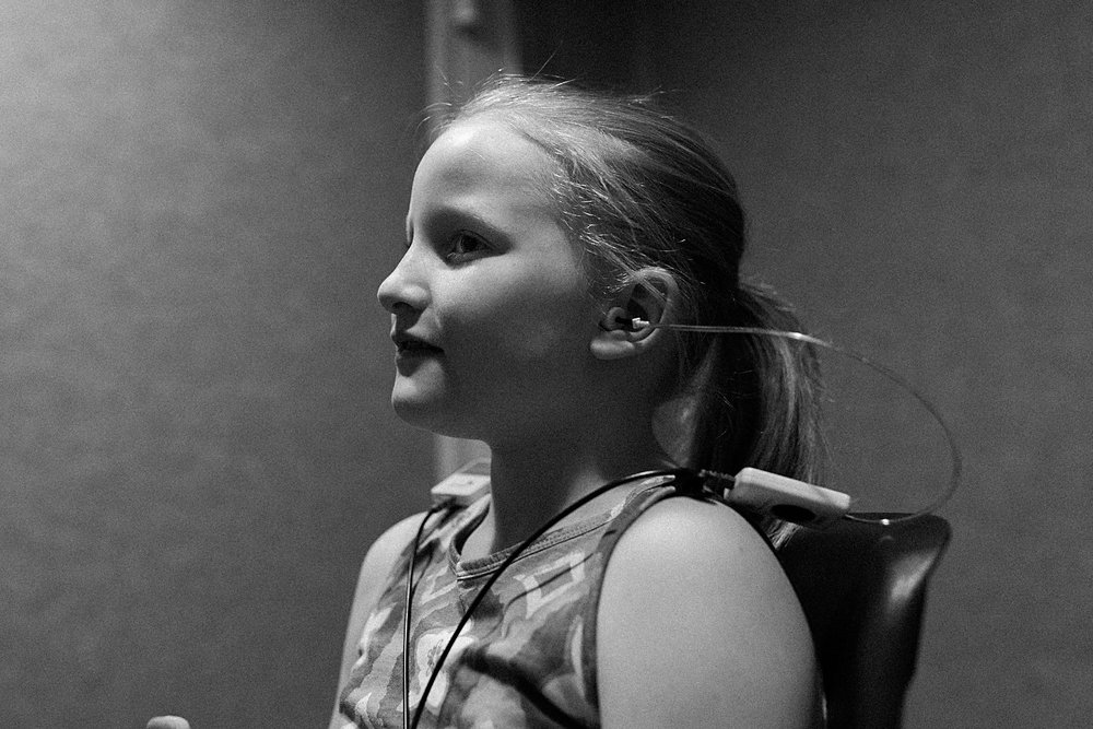 girl sits in sound proof room while listening to sounds piped into ears