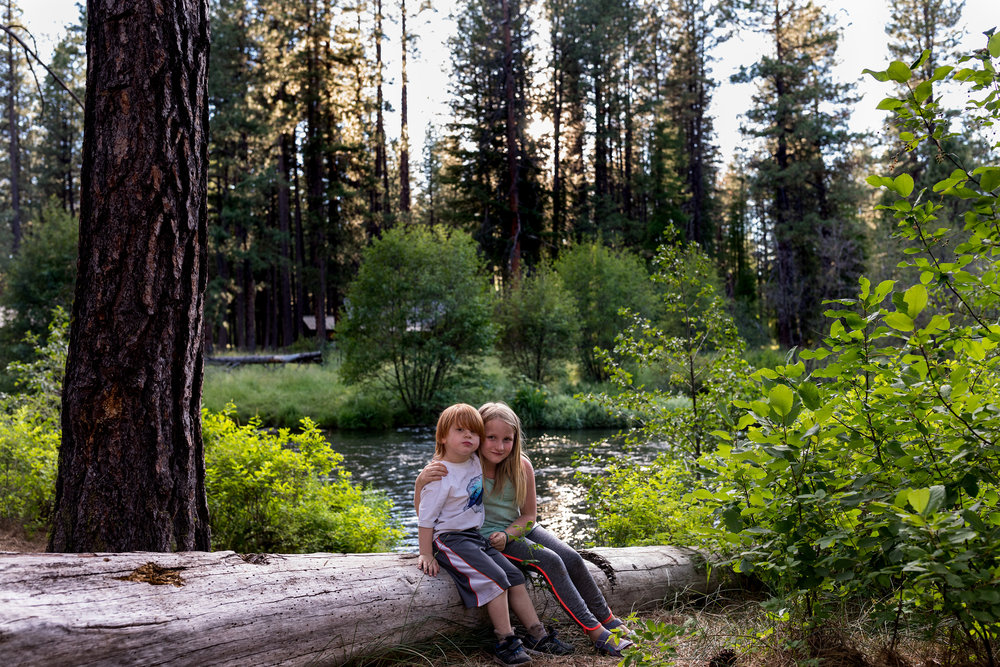 cousins sit on a log together near the river