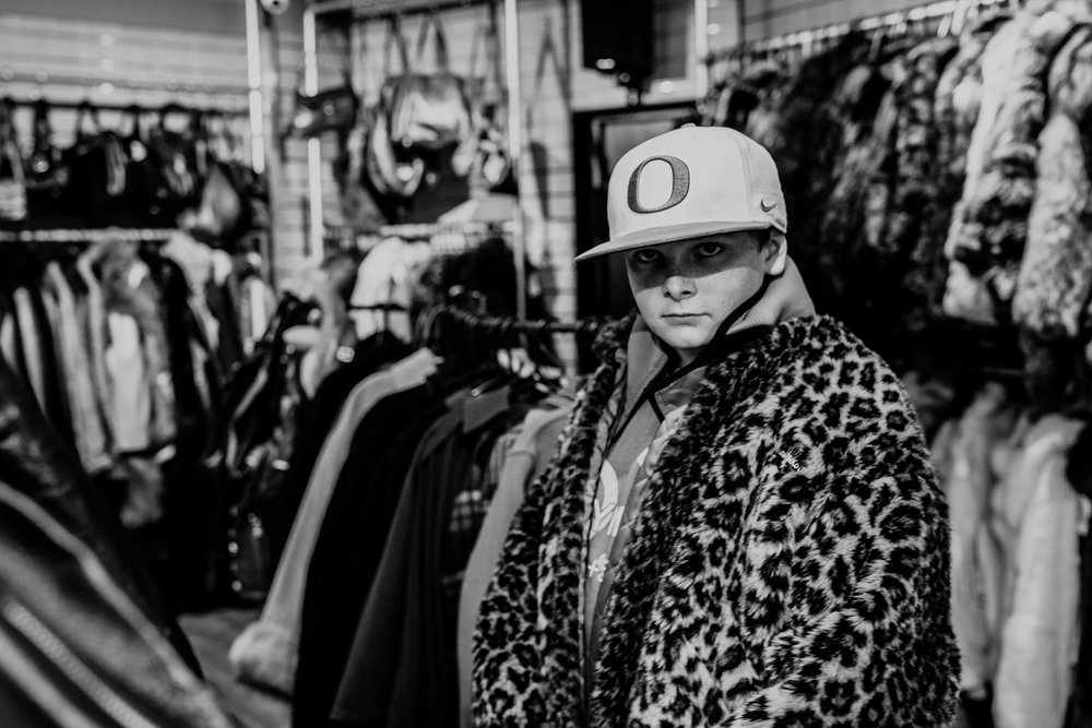 A boy wears a fake fur cheetah coat and Oregon Ducks hat in thrift shop. London, England.