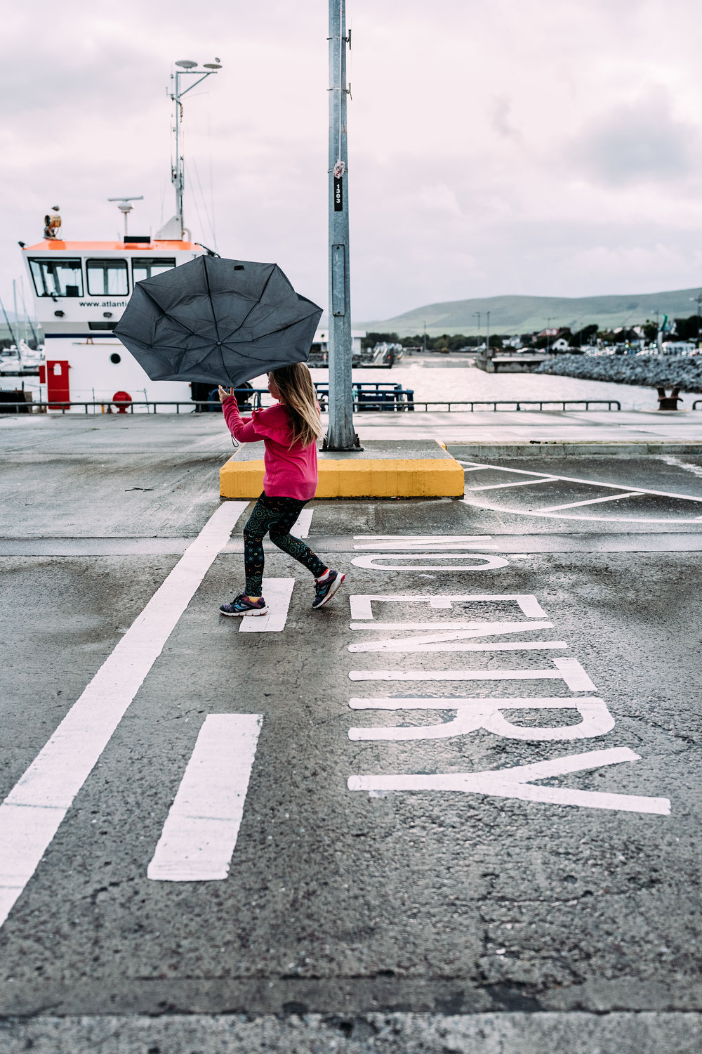 A strong wind blows a girl's umbrella inside out on a dockside in Dingle, Ireland