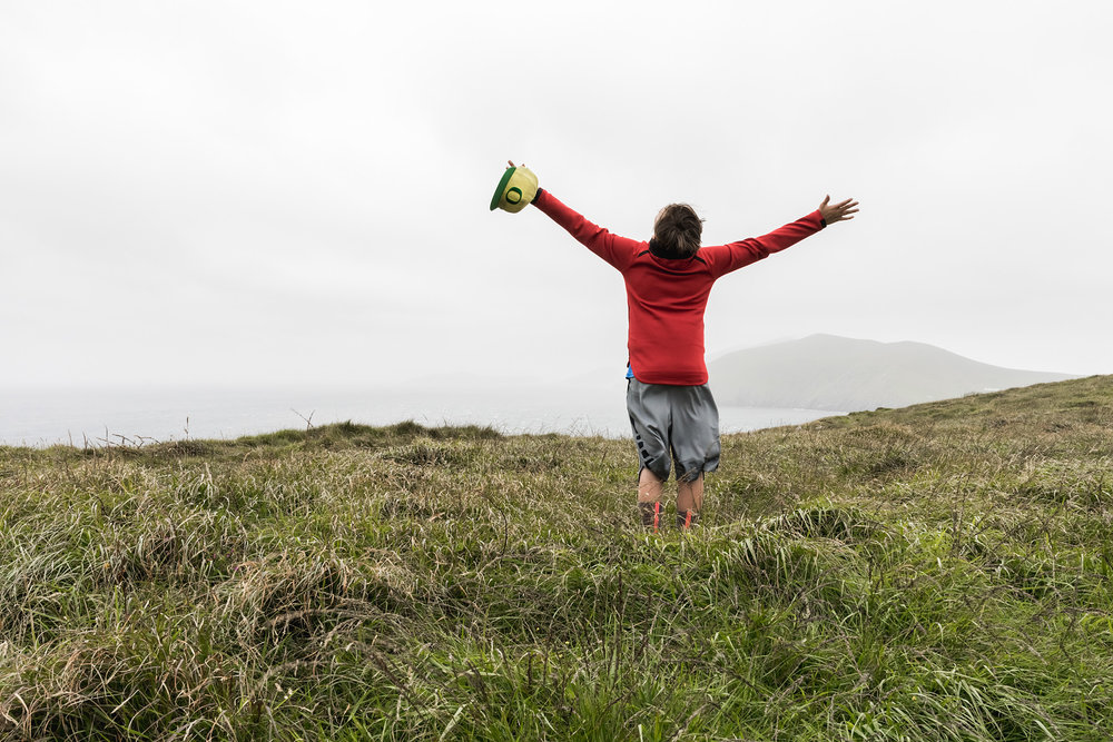 A boy throws his arms wide as the wind off the Irish cliffs whip around him