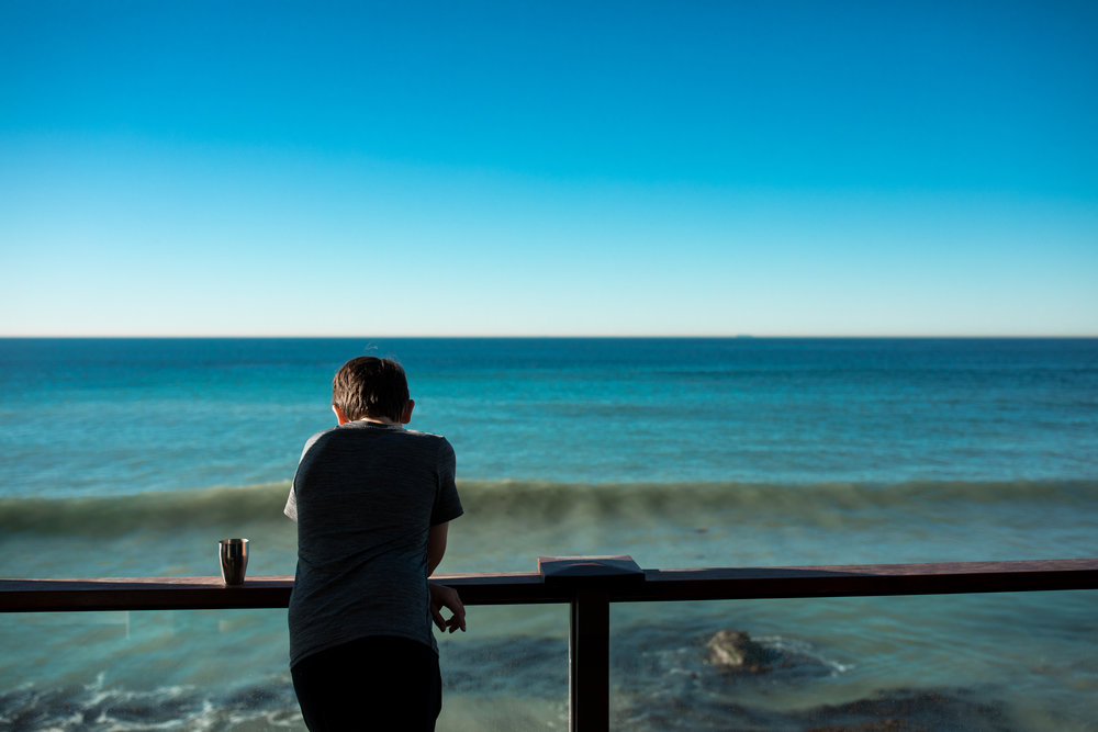 boy looks out onto Pacific Ocean on a clear day
