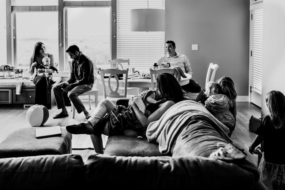 Extended family gathers around living room with young children.