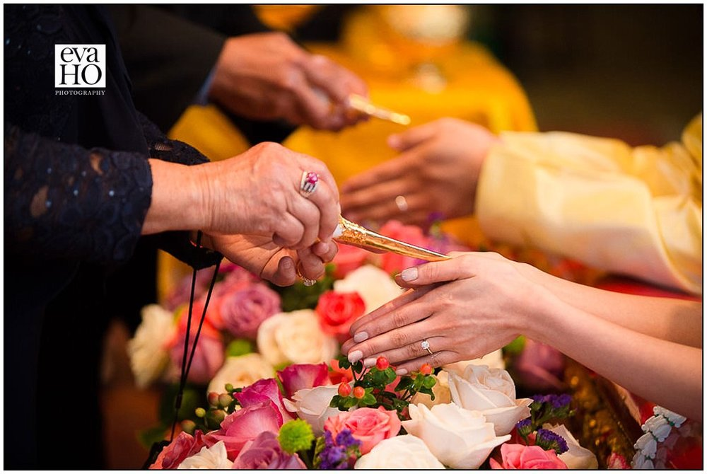 Guests drips water down the hands of the newly wed as a blessing during the Thai Water Ceremony