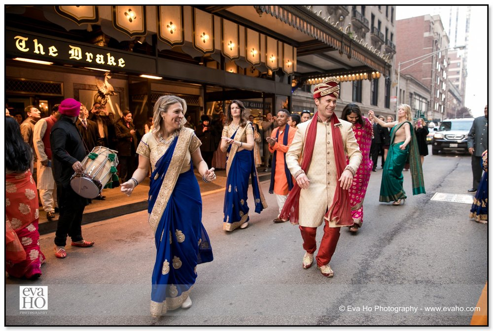 Groom dances with his wedding guests outside The Drake hotel in Chicago during the baraat.