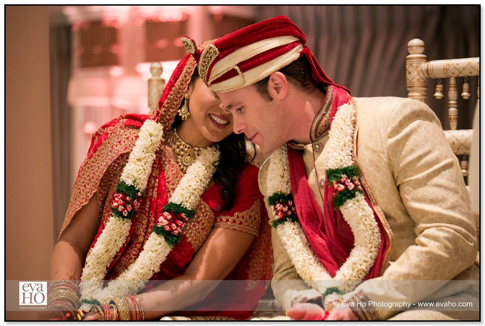 Bride and Groom whisper to each other during a traditional Indian ceremony in Chicago.
