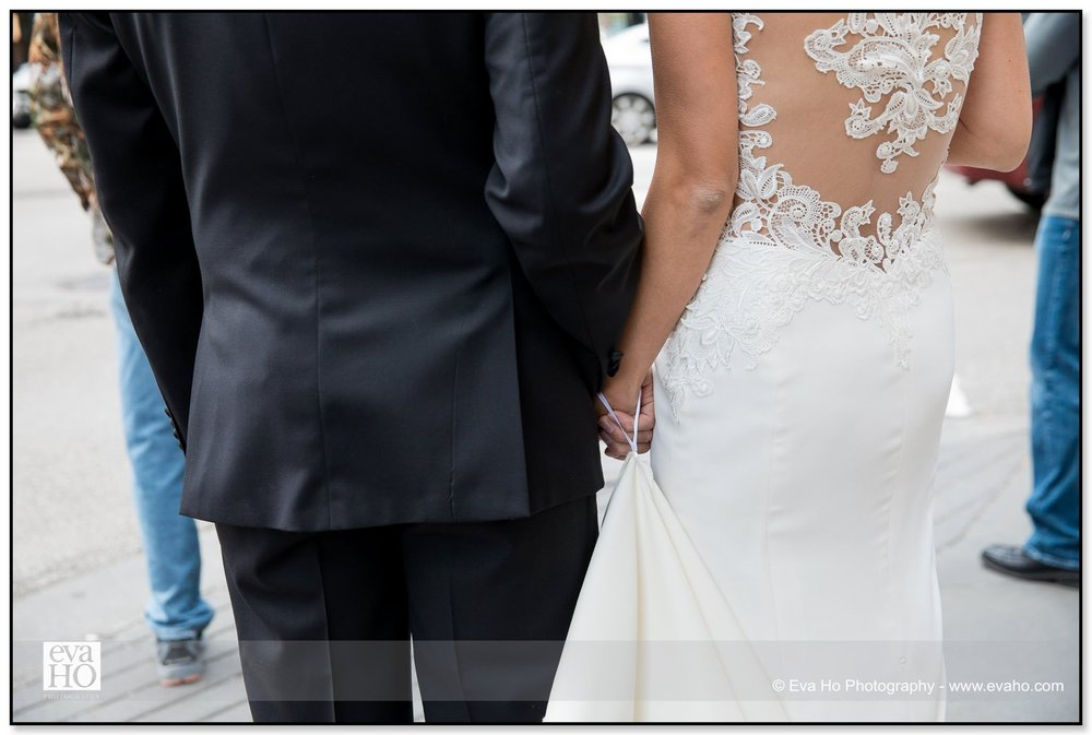 Details shot of a bride and groom holding hand and the gorgeous lace back of the bride's classic wedding dress