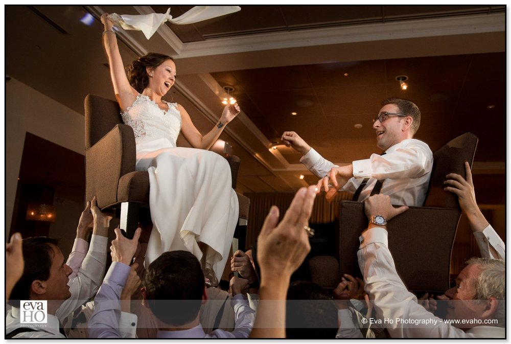 Wedding guests lift bride and groom up into the air on their chairs during a Jewish wedding at Chicago's Ivy Room