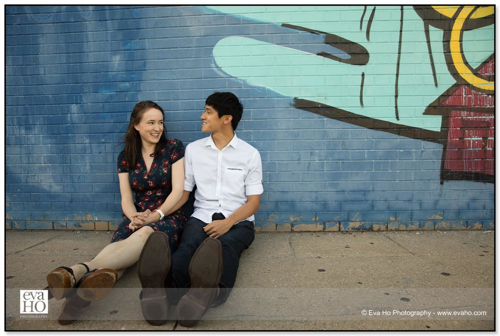 Couple sitting next to mural near Logan square for engagement session portraits