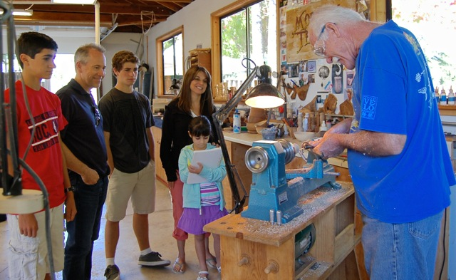 Visitors to Open Studios enjoy watching jerry turn colorful tops for the kids.