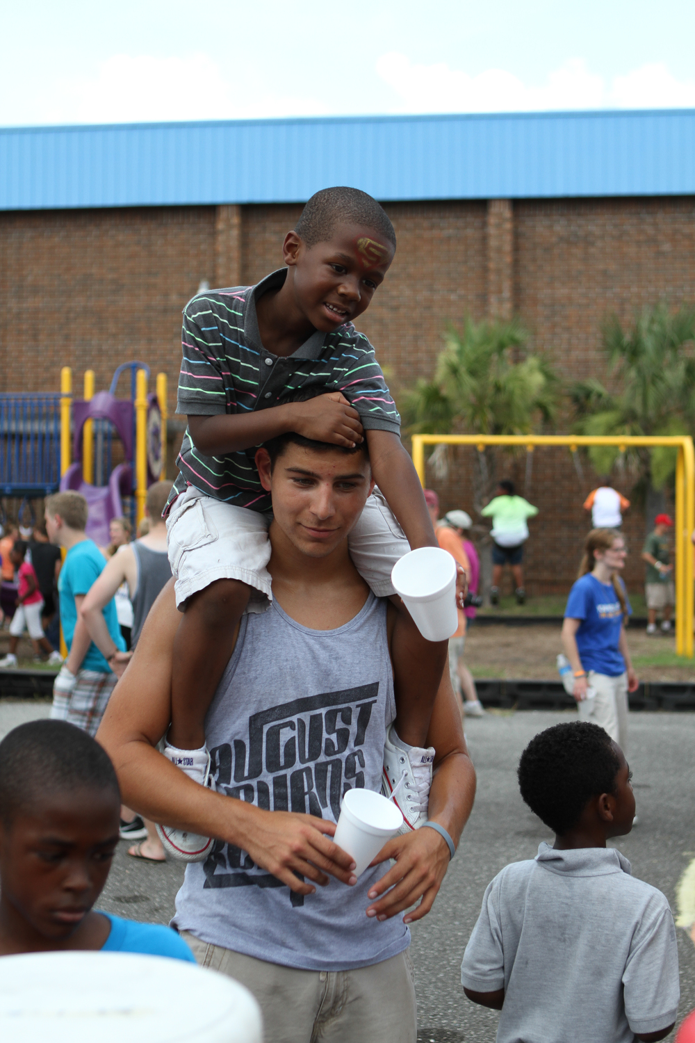 A student plays with a kid attending our Boys & Girls Club fun day.