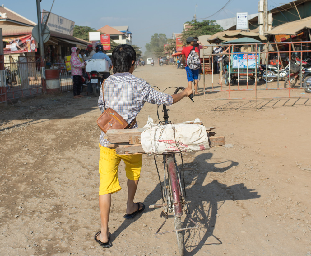 Young khmer boy pushing bicycle