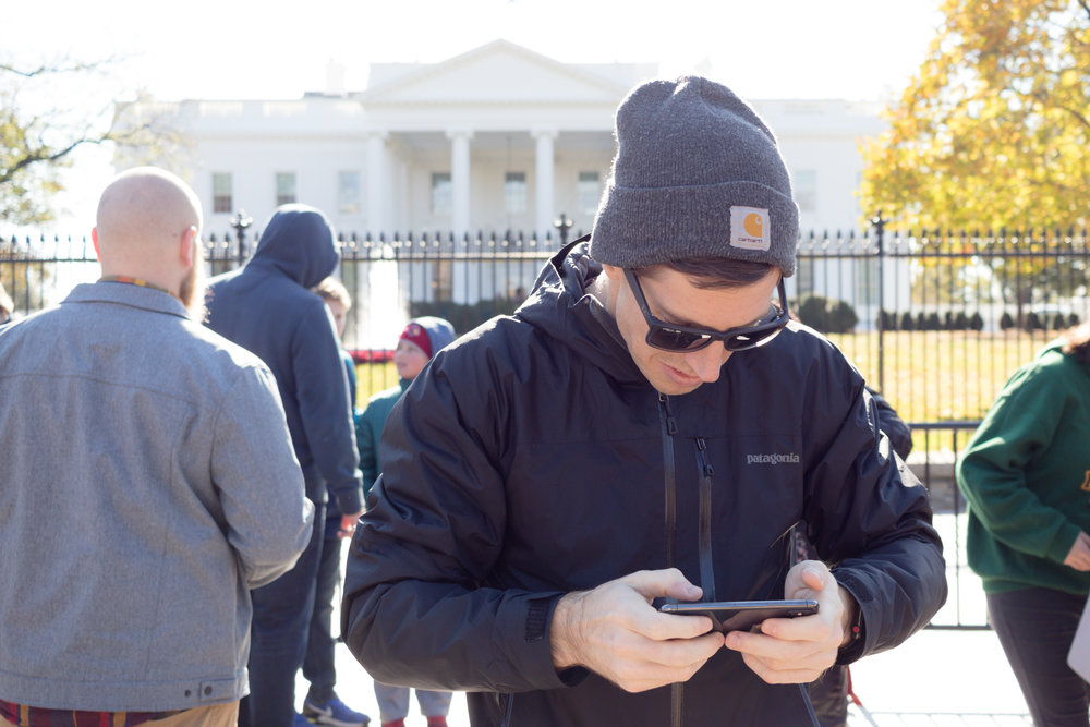 Shay on his phone in front of an important government building (Photo 1 of 3)