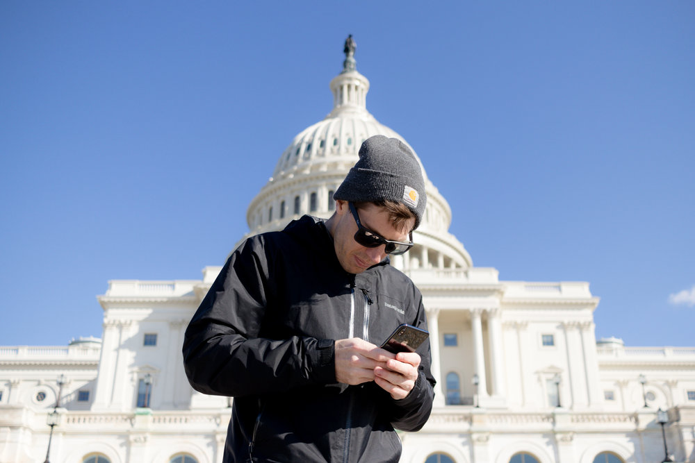 Shay on his phone in front of an important government building (Photo 2 of 3)