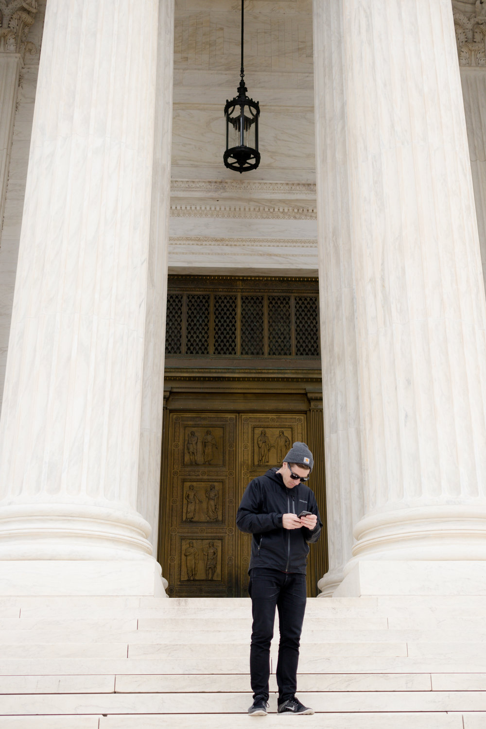 Shay on his phone in front of an important government building (Photo 3 of 3)
