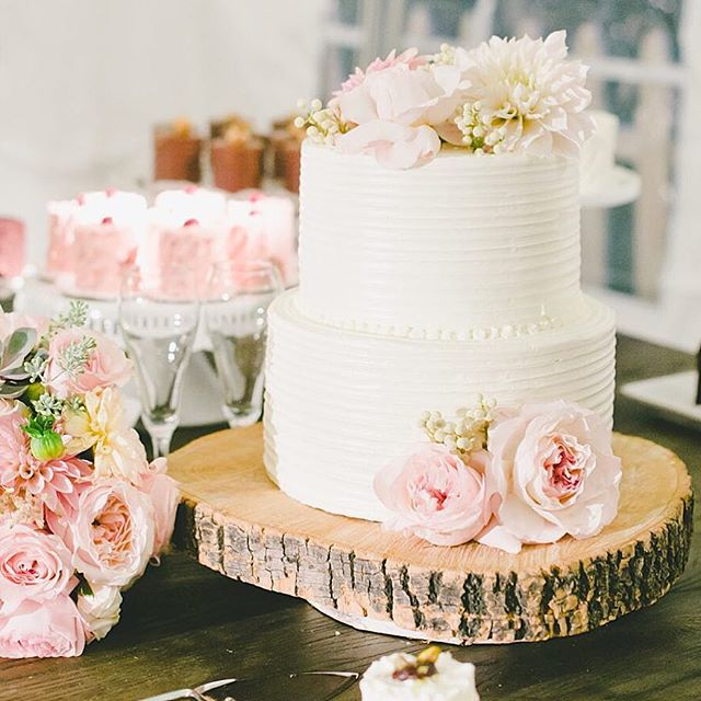 Simple and classic, this two-tiered cake topped with fresh peonies and dahlias looks almost rustic when placed atop a round of wood / 🍰: @cakemonkeybakery Click link in bio for more of this #BridesRealWedding